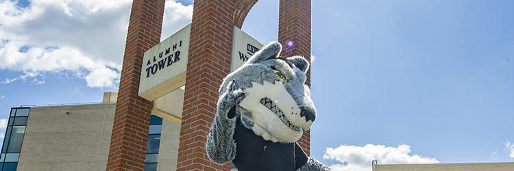 photo of rowdy in front of alumni tower