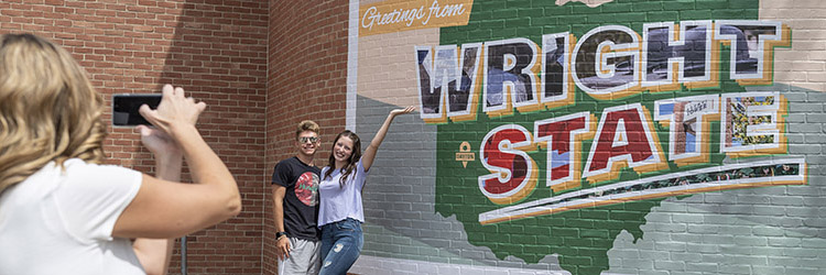 photo of people taking a photo in front of the welcome to wright state mural